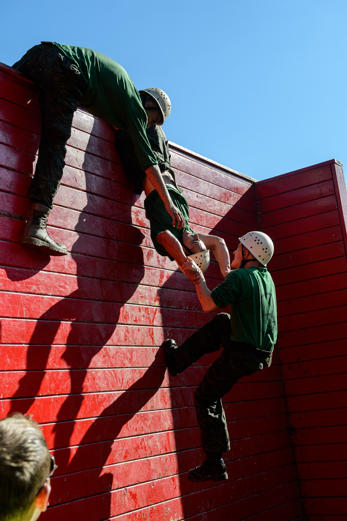 Officer Cadets work together to overcome the obstacle course