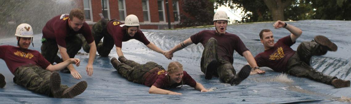 Des élèves-officiers du CMR glissent sur un obstacle d'eau